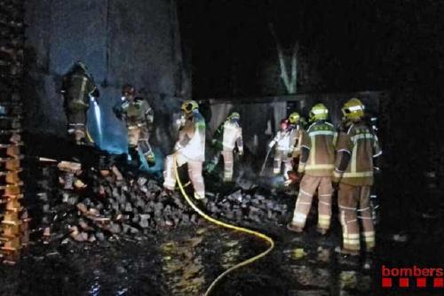 Els Bombers apaguen un foc declarat a l'exterior d'una fàbrica de palets situada al costat de la B-140